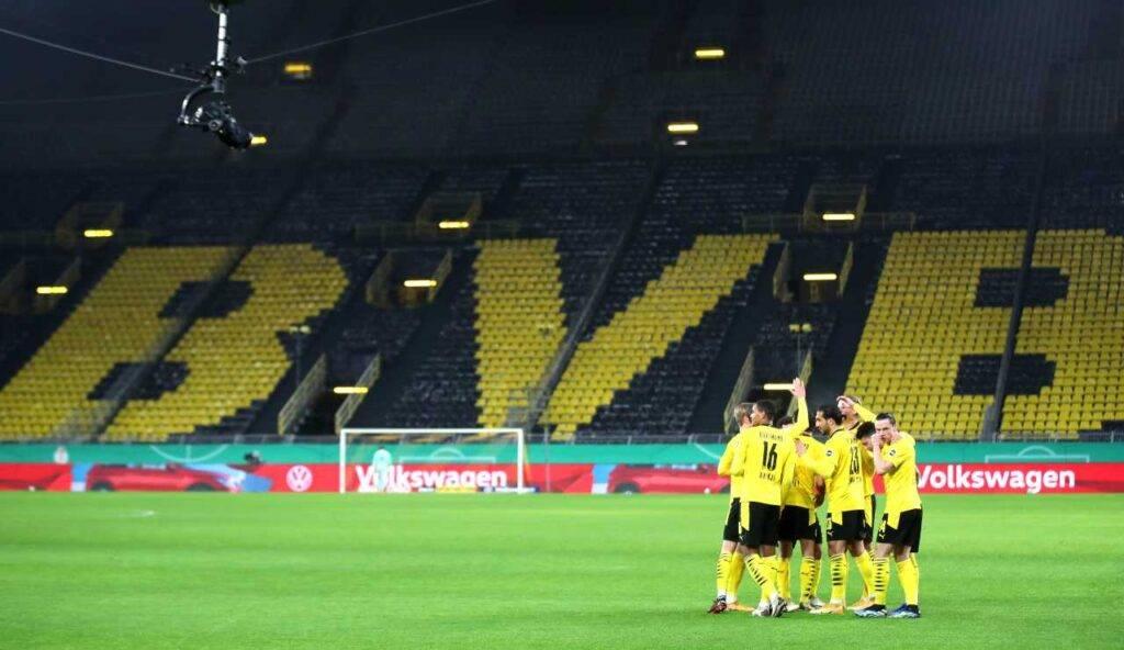 I giocatori del Borussia esultano in uno stadio tristemente vuoto
