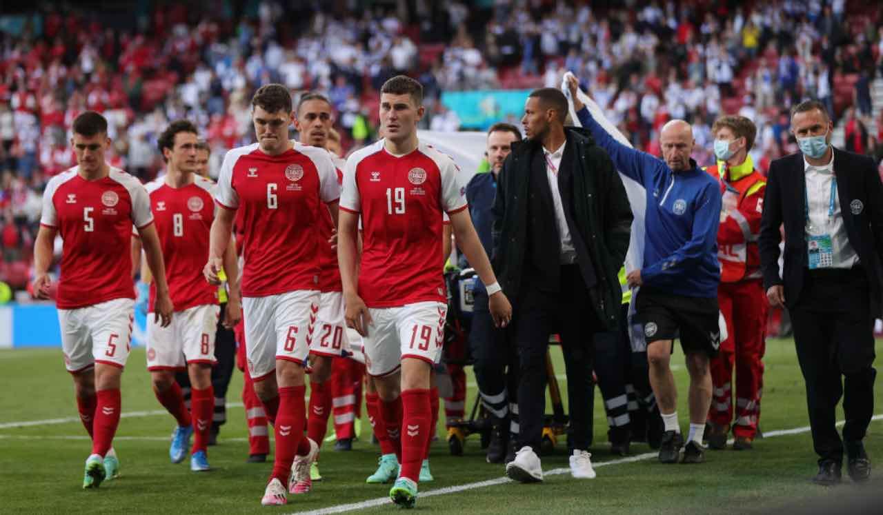I giocatori della Danimarca scortano l'uscita dal campo di Eriksen